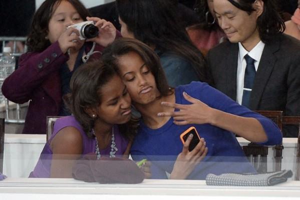 As filhas do casal Obama, Sasha (esq.) e Malia, fazem pose de 'rappers' para foto com o celular durante desfile celebrando a posse do pai. (Foto: Joe Klamar/AFP)